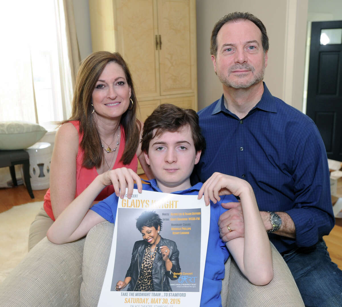 Phil and Andrea Marella with their son, Andrew Marella, 15, holding a Gladys Knight poster at their Greenwich home, Friday, May 8, 2015. Andrew Marella suffers from Niemann-Pick Type C, a genetic disease that is a neurodegenerative disorder which causes progressive deterioration of the nervous system. The family who also lost a daughter, Dana, to the disorder, is spearheading a benefit gala featuring Kinght at the Palace Theatre in Stamford on Saturday, May 30, to raise money and awareness for medical research of Niemann-Pick Type C.