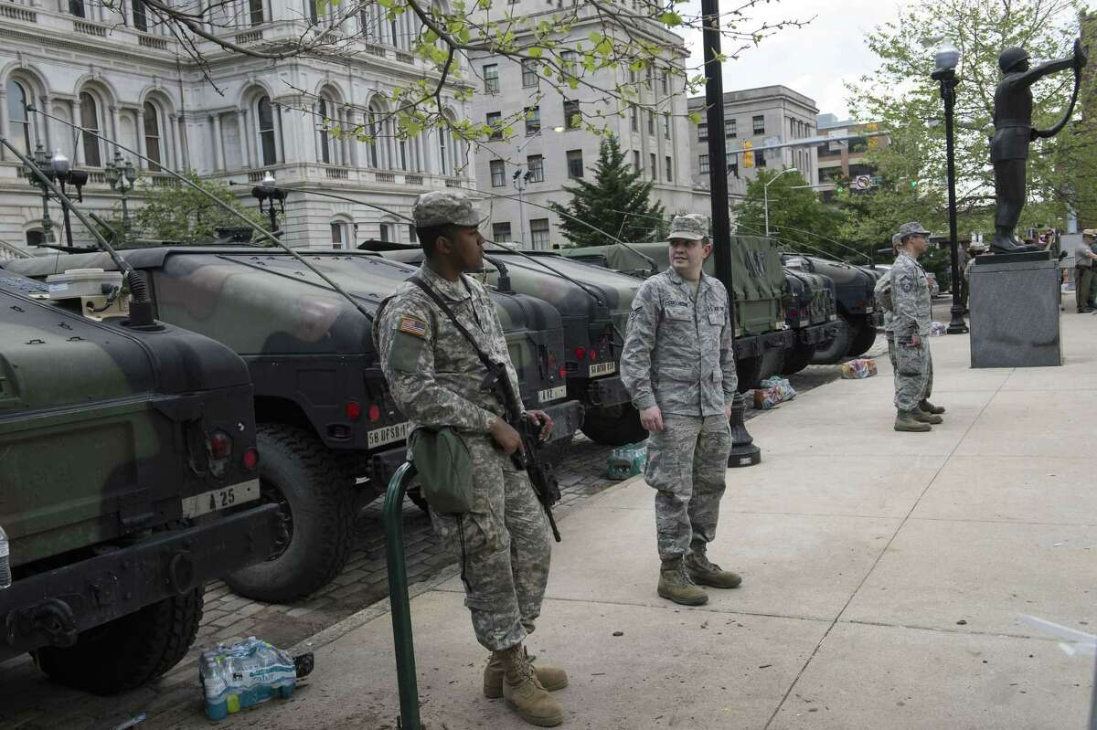 Members of the National Guard stand in front of City Hall in Baltimore on May 3. The answer isn't more social programs, what Democrats suggest.