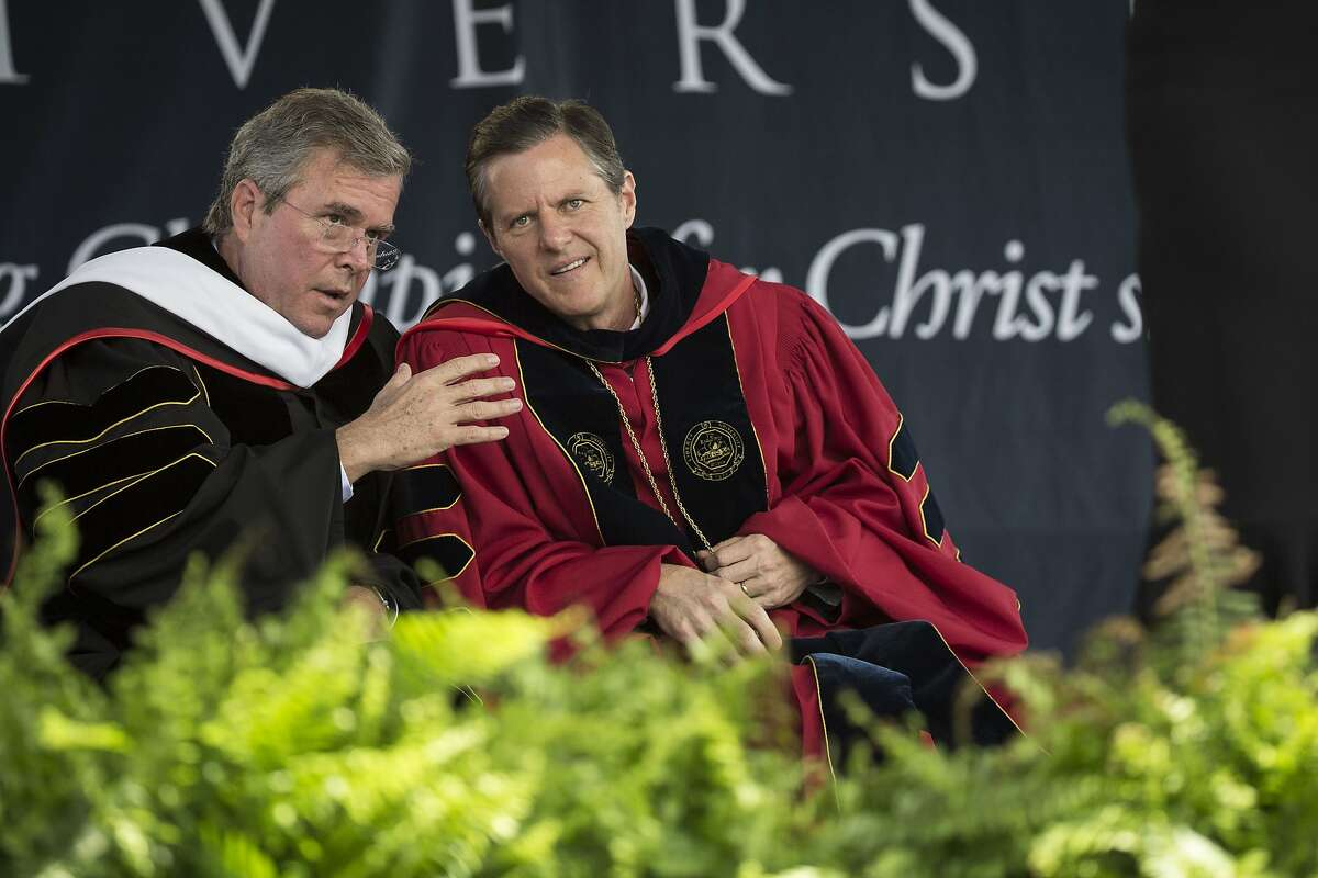 """(L to R) Republican U.S. presidential hopeful and former Florida governor Jeb Bush and Liberty University president Rev. Jerry Falwell Jr. talk with each other during the commencement ceremony at Liberty University, at Williams Stadium on the campus of Liberty University, May 9, 2015 in Lynchburg, Virginia. In his remarks, Bush criticized the Obama administration for being """"small minded and intolerant"""" of religious freedom. (Drew Angerer/Getty Images) *** BESTPIX ***"""