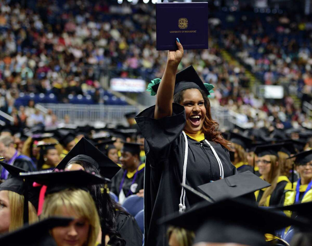 Graduate Elizabeth De Los Santos, of Bronx, N.Y., waves her diploma in the air during the University of Bridgeport's 105th commencement ceremony Saturday, May 9, 2015 at the Webster Bank Arena in Bridgeport, Conn.