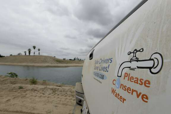 In this May 6, 2016 file photo, a sign urges water conservation in front of recycled wastewater in a holding pond used to recharge an underground aquifer at the Orange County Water District recharge facility in Anaheim, Calif. The water district, which serves 2.4 million people near Los Angeles, wants credit for sending wastewater through ground basins for drinking, as they face statewide cuts to urban water use approved this month.  (AP Photo/Chris Carlson)