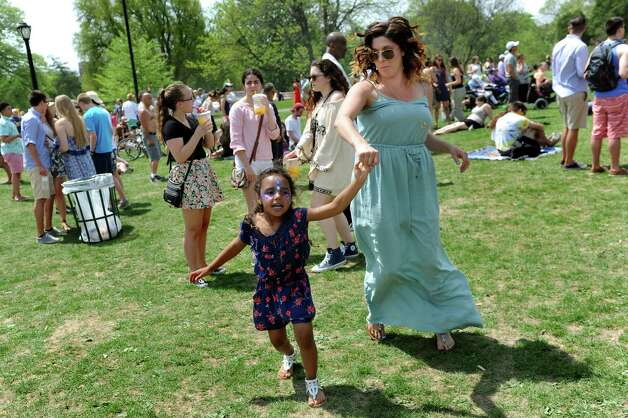 Adrianna Edwards, 4, of Albany, center, dances with her mother, Elise Fish, to the music of Flagship at the main stage during the 67th Annual Tulip Festival on Saturday, May 9, 2015, at Washington Park in Albany, N.Y. (Cindy Schultz / Times Union) Photo: Cindy Schultz / 00031726A