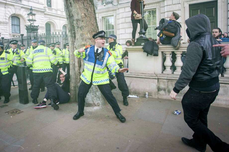Police confront protesters outside Downing Street during a demonstration against the Con- servative government Saturday, a day after the Tories won Britain's parliamentary elections. Photo: Rick Findler / Associated Press / PA