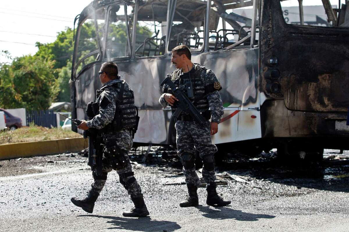 FILE - In this May 1, 2015 file photo, state police stand next to a charred passenger bus, that was extinguished by firefighters in Guadalajara, Mexico. Authorities in western Mexico asked residents to stay at home as they scrambled to extinguish burning vehicles that blocked roads in various parts of Guadalajara. Such blockades are a common cartel response to the arrest of important members or are used to foil police and military operations.