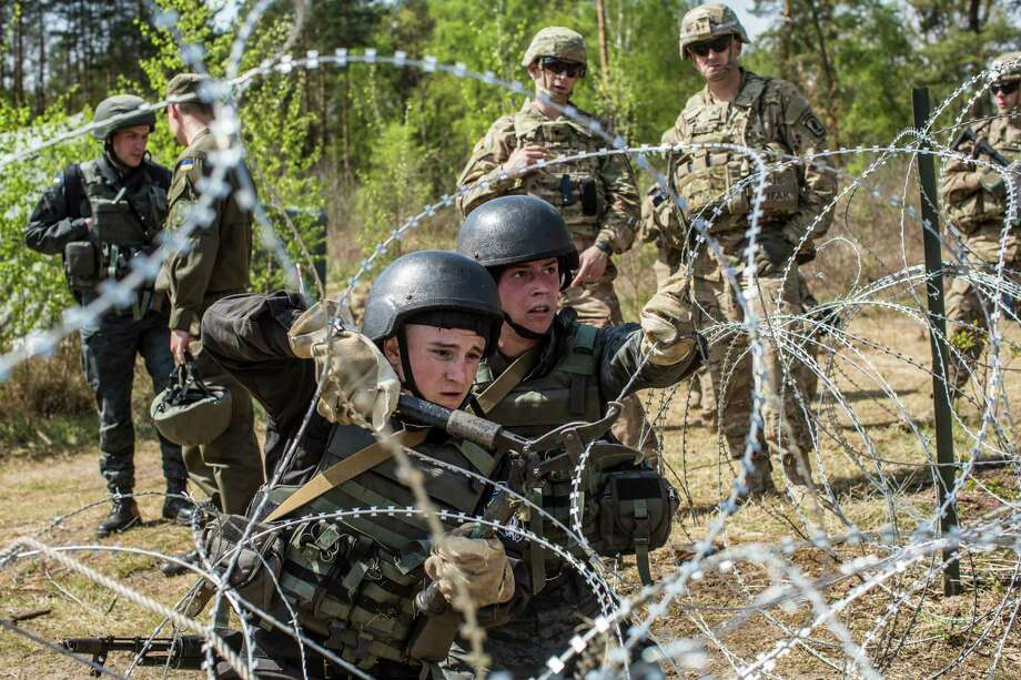 Watched by trainers from the U.S. Army, Ukrainian soldiers participate in a wire-cutting exercise in Yavoriv, Ukraine. Photo: Brendan Hoffman /New York Times / NYTNS