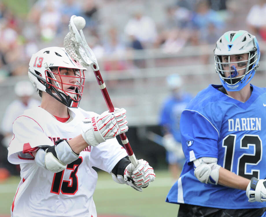 Peter Swindell (#13) of New Canaan, left, shoots while being defended by Darien's Ian Burgoyne (#12) during the boys high school lacrosse match between New Canaan High School and Darien High School at New Canaan, Conn., Saturday, May 9, 2015. New Canaan defeated Darien, 9-8. Photo: Bob Luckey / Greenwich Time