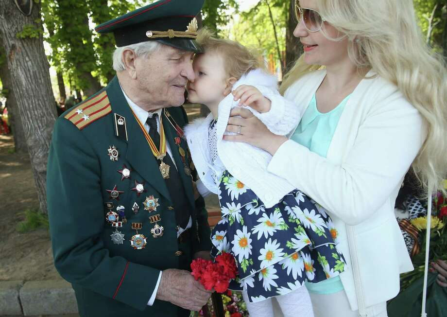 Ivan Masyeyevich Kazantsev, 93, who fought in World War II with the Soviet Red Army against the Japanese in northern China, snuggles a child during Victory Day celebrations. Photo: Sean Gallup /Getty Images / 2015 Getty Images