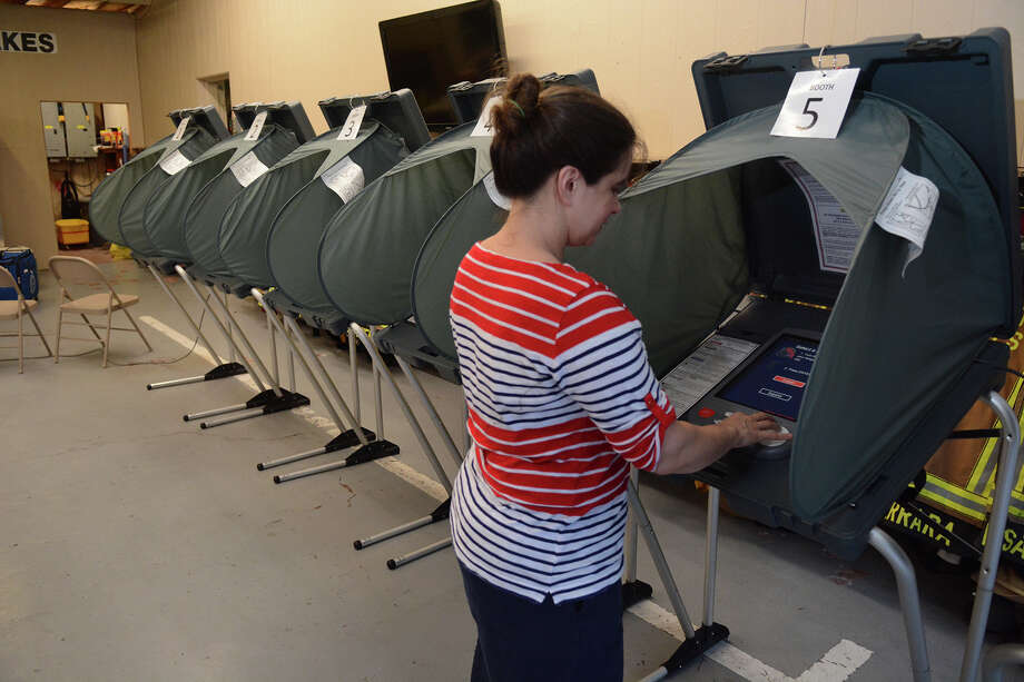 Chelsea Taylor, Alternate Election Judge at the polling location for Precincts 32, 45 & 84 at the Timber Lakes/Timber Ridge Fire Station in Spring, checks out the voting machines before opening the polling location on Saturday, May 9, 2015. Photo: Jerry Baker, For The Chronicle