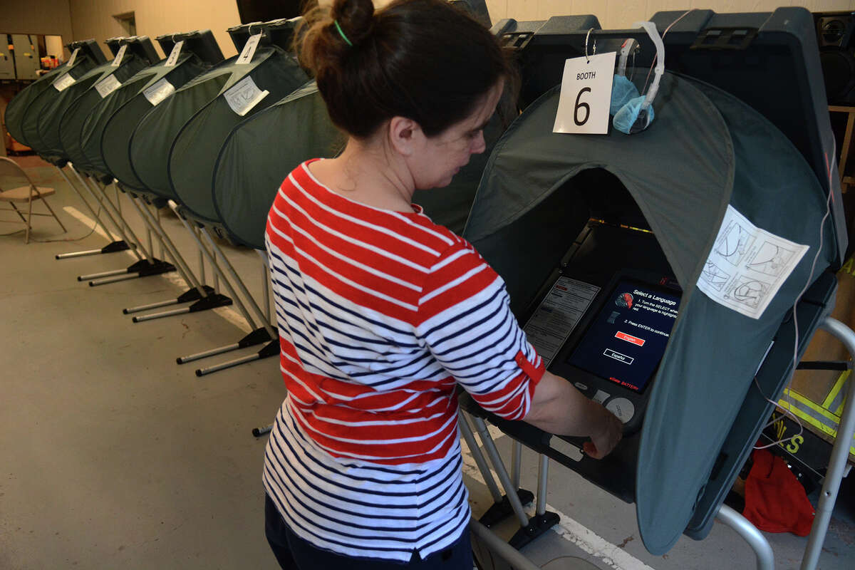 Chelsea Taylor, Alternate Election Judge at the polling location for Precincts 32, 45 & 84 at the Timber Lakes/Timber Ridge Fire Station in Spring, checks out the voting machines before opening the polling location on Saturday, May 9, 2015.