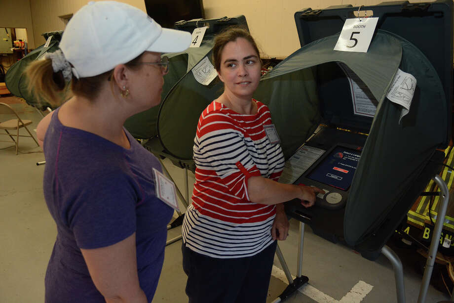 Shelly Rollins, from left, poll worker, and Chelsea Taylor, Alternate Election Judge at the polling location for Precincts 32, 45 & 84 at the Timber Lakes/Timber Ridge Fire Station in Spring, check out the voting machines before opening the polling location on Saturday, May 9, 2015. Photo: Jerry Baker, For The Chronicle