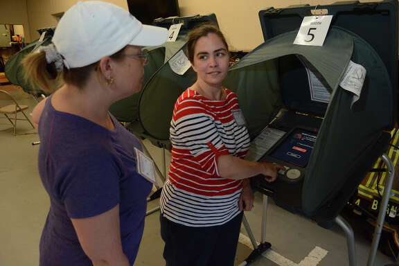 Shelly Rollins, from left, poll worker, and Chelsea Taylor, Alternate Election Judge at the polling location for Precincts 32, 45 & 84 at the Timber Lakes/Timber Ridge Fire Station in Spring, check out the voting machines before opening the polling location on Saturday, May 9, 2015.