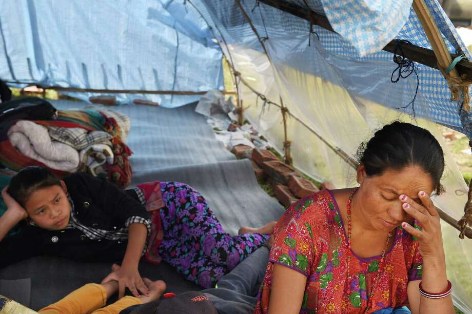 """Maindi Moltan, 35, right, a mother of three who is eight months pregnant, sits in a tent along with Sustari Tamang and others at an encampment for people displaced by the earthquake. """"I wish I had my cooking pots, but I barely saved myself and my children,"""" she said Moltan.  Photo: POST, STF / The Washington Post"""
