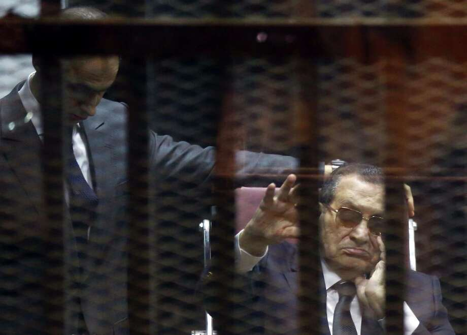Ousted Egyptian president Hosni Mubarak (R) waves from the defendants cage next to one of his son's Gamal as they listen to the verdict in their hearing in a retrial for embezzlement on May 9, 2015 in Cairo. The Egyptian court sentenced Mubarak and his two sons to three years in prison.  AFP PHOTO / MOSTAFA EL-SHEMYMOSTAFA EL-SHEMY/AFP/Getty Images Photo: MOSTAFA EL-SHEMY, Stringer / AFP / Getty Images / AFP