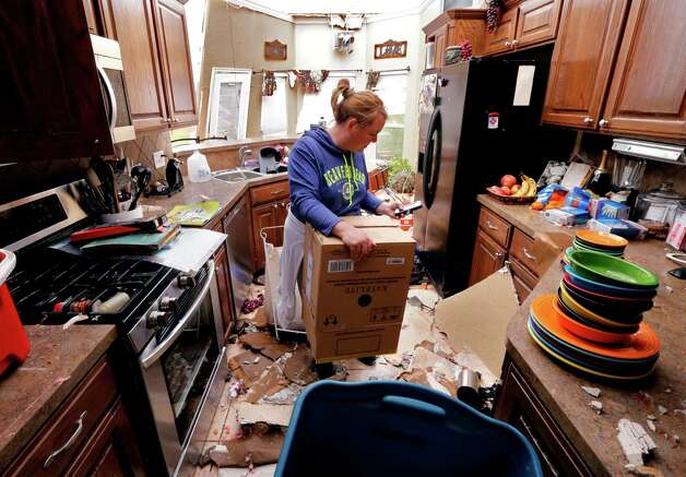Jennifer Moon recovers kitchen items by the light of the sky on Thursday, May 7, 2015, in Bridge Creek, Okla. Wednesday's storm took off the roof. Communities in several southern Plains states set to work cleaning up Thursday after a night of storms that spawned dozens of tornadoes, assessing the damage under sunny skies but with the threat of even worse weather on the horizon. (Steve Sisney/The Oklahoman via AP) ORG XMIT: OKOKL112 Photo: STEVE SISNEY / The Oklahoman