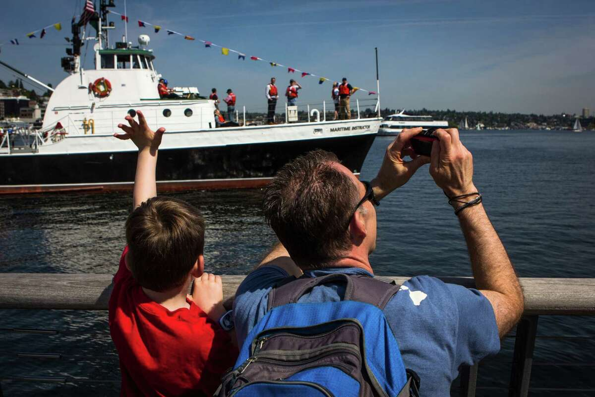 Rob and Drew Norlin watch the Workboat Parade during the Vigor Seattle Maritime Festival at Lake Union Park on Saturday, May 9, 2015. The event included a Workboat parade, tours of Lake Union, survival suit races, the Workboat World Invitational Boat Building Competition, and many other maritime activities.