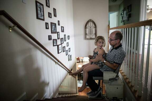 Jay Smith and his daughter, Peyton, ride a stair lift at their home in Austin last week. Smith said he fears a right-to-try law won't help ALS patients because the FDA's fast-track drug program doesn't.