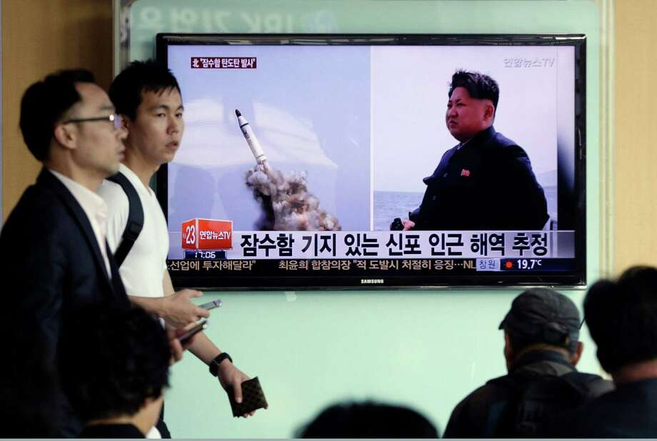 """South Korean men pass by a TV news program showing images published in North Korea's Rodong Sinmun newspaper of North Korea's ballistic missile believed to have been launched from underwater and North Korean leader Kim Jong-un, at Seoul Railway station in Seoul, South Korea, Saturday, May 9, 2015. North Korea said Saturday it has successfully test-fired a newly developed ballistic missile from a submarine in what would be the latest display of the country's advancing military capability. The letters on the screen read """"The missile believed to have been launched from underwater near Sinpo"""".  (AP Photo/Ahn Young-oon) Photo: Ahn Young-joon, STF / AP"""