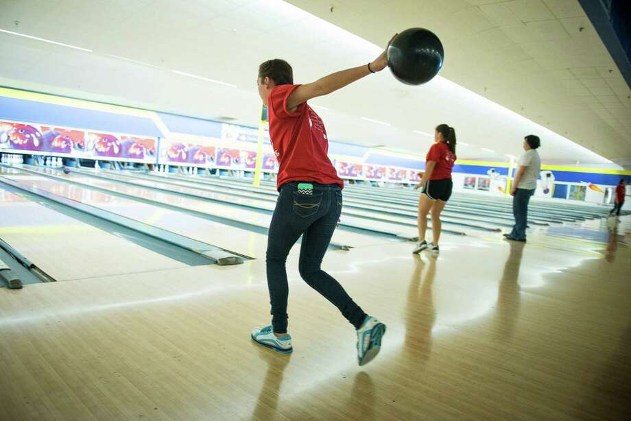 Marisa Hirschmann, 16, a Health Careers High School bowler and state-champion with the Northside district team, practices at Bandera Bowling Center in San Antonio on Tuesday, April 27, 2015. Hirschmann was diagnosed with Ewing Sarcoma, a bone cancer, in April 2009. After undergoing 12 months of chemo treatment and an invasive surgery on her right side which replaced some of the bone in her shoulder and arm, Hirschmann has been in remission now for five years. She was an avid right-handed bowler before being diagnosed, and after her surgery taught herself how to bowl left-handed. She says she liked it because she was good at it, and could get better. Photo: Matthew Busch, For The San Antonio Express-News / For San Antonio Express-News / © Matthew Busch