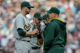 SEATTLE, WA - MAY 09:  Starting pitcher Jesse Hahn #32 of the Oakland Athletics gets a visit from pitching coach Curt Young #41 after falling behind 2-0 against the Seattle Mariners in the first inning at Safeco Field on May 9, 2015 in Seattle, Washington.  (Photo by Otto Greule Jr/Getty Images)