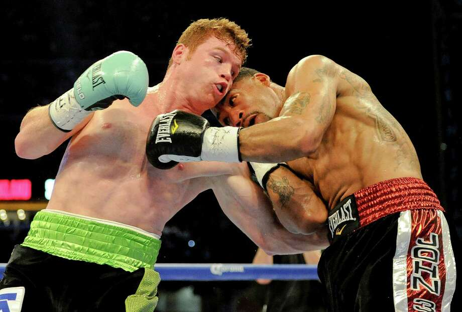 Canelo Alvarez, left, punches James Kirkland during the first round of their super welterweight match, Saturday, May 9, 2015, at Minute Maid Park in Houston. Alvarez won the fight with a knockout in the third round. Photo: Eric Christian Smith, Eric Christian Smith/For The Chr / 2015 Eric Christian Smith