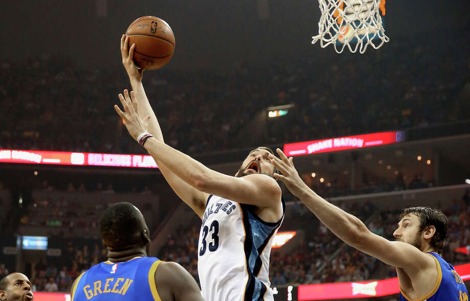 Grizzlies center Marc Gasol, who had 21 points, flips up a shot against Draymond Green and Andrew Bogut. Photo: Andy Lyons / Getty Images / 2015 Getty Images