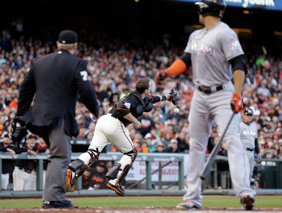 Buster Posey is unable to catch Giancarlo Stanton's foul ball in the third inning. Stanton then struck out, stranding two. Photo: Ben Margot / Associated Press / AP