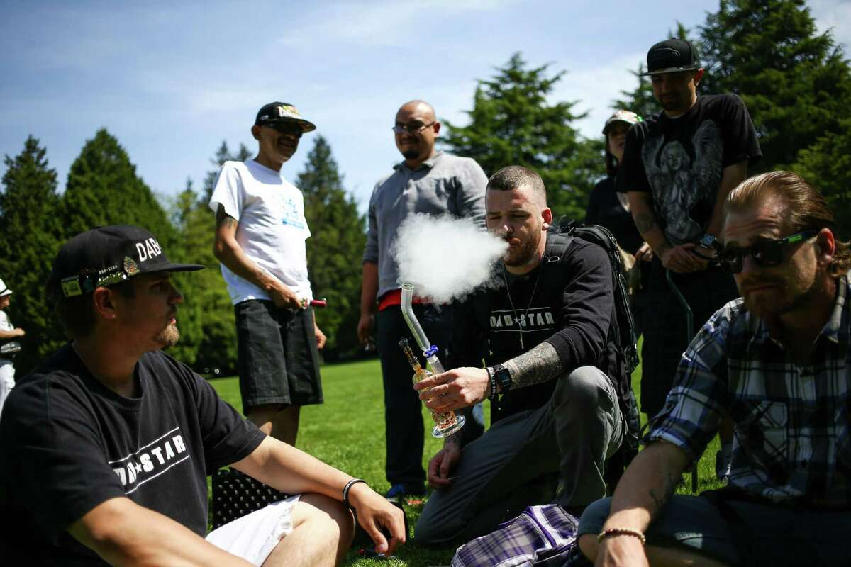 People vaporize marijuana during the annual Cannabis Freedom March from Capitol Hill's Volunteer park to Westlake in downtown Seattle. About 100 people marched to voice their displeasure with what appears to be the end of medical marijuana and a shift to a state-controlled system based on recreational marijuana. Photographed on Saturday, May 9, 2015.