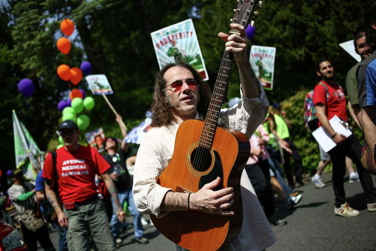 A participant plays his guitar during the annual Cannabis Freedom March from Capitol Hill's Volunteer park to Westlake in downtown Seattle. About 100 people marched to voice their displeasure with what appears to be the end of medical marijuana and a shift to a state-controlled system based on recreational marijuana. Photographed on Saturday, May 9, 2015.