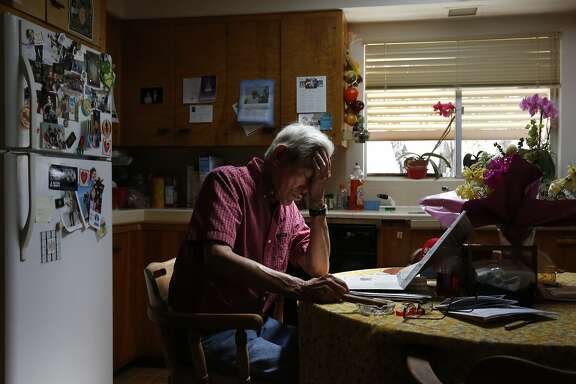 "Robert Ishida, 93, reads the daily paper while smoking a cigar at a table adorned with Easter flowers that he purchased for his late wife of 60 years at his home where he now lives alone April 17, 2015 in Lindsay, Calif. The Ishida family first starting farming citrus in the early 1900s and are now on their third generation of citrus farmers. This year the family will be ""pushing out"" at least 35 acres of citrus trees that were among the first Robert planted after he purchased new land in the early 1950s."
