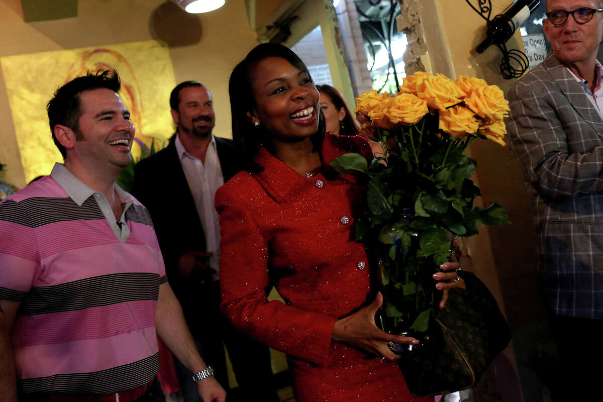 Mayor Ivy Taylor arrives at her election watch party at SoLuna where Gerardo Calvillo, left, an owner of SoLuna, his family's business, presented her with two dozen yellow roses in San Antonio on Saturday, May 9, 2015.