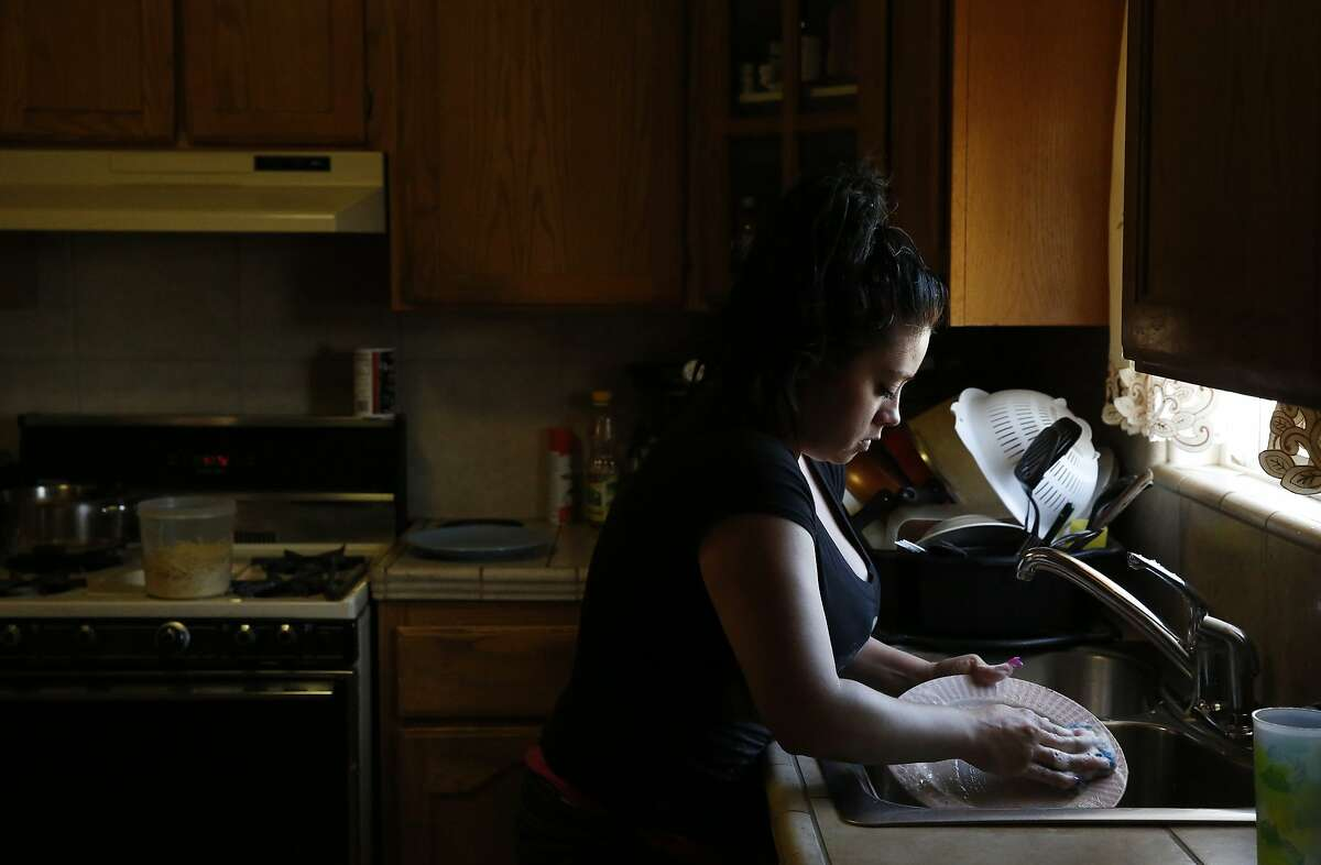 Lizette Serrato, 25, does the dishes after dinner at her home April 13, 2015 in Porterville, Calif. Yolanda Serrato's well ran dry while she was watering her lawn in the summer of 2014. Her family recently received a large tank that holds about two weeks worth of non-potable water. More than 500 wells have gone dry in East Porterville since the beginning of the drought four years ago. The Porterville Area Coordinating Council has provided homes that have run out of water with 300-gallon tanks and the city has been filling them while the county replaces the small tanks with larger 1,500-2,500 tanks as part of the county?•s household tank program. The larger tanks are filled every two weeks and the city has also been providing residents who sign up for the program with bottled water.