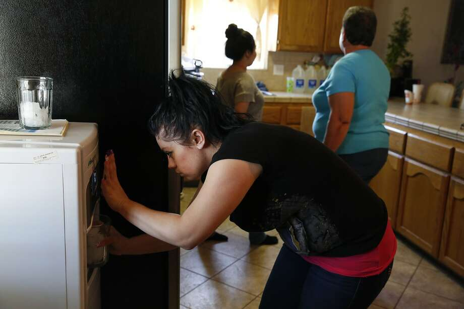 "Lizette Serrato, 25, fills up glasses with drinking water for dinner using a City Council donation, a ""DewPointe"" machine that converts humidity from the air into water at the Serrato home in Porterville (Tulare County). Yolanda Serrato's well ran dry while she was watering her lawn in the summer of 2014. Her family recently received a large tank that holds about two weeks' worth of nonpotable water. More than 500 wells have gone dry in East Porterville since the beginning of the drought four years ago. The Porterville Area Coordinating Council has provided homes that have run out of water with 300-gallon tanks and the city has been filling them while the county replaces the small tanks with larger 1,500-2,500-gallon tanks as part of the county's household tank program. The larger tanks are filled every two weeks and the city has also been providing residents who sign up for the program with bottled water. Photo: Leah Millis, The Chronicle"