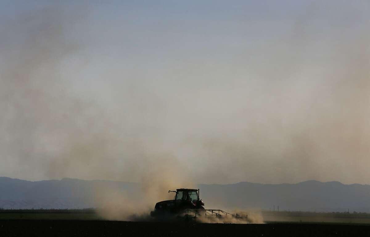 Alfredo Reynosa prepares a field for tomatoes April 9, 2014 near Lemoore, Calif.