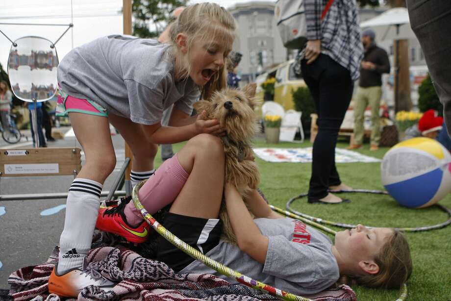 Margo Tellini (left), 8, and Madeline Podell, 8, play with their dog Stella in the grass of the AirBnB booth during the Mission Sunday Streets festival Sunday, May 10, 2015. Photo: Jessica Christian, The Chronicle
