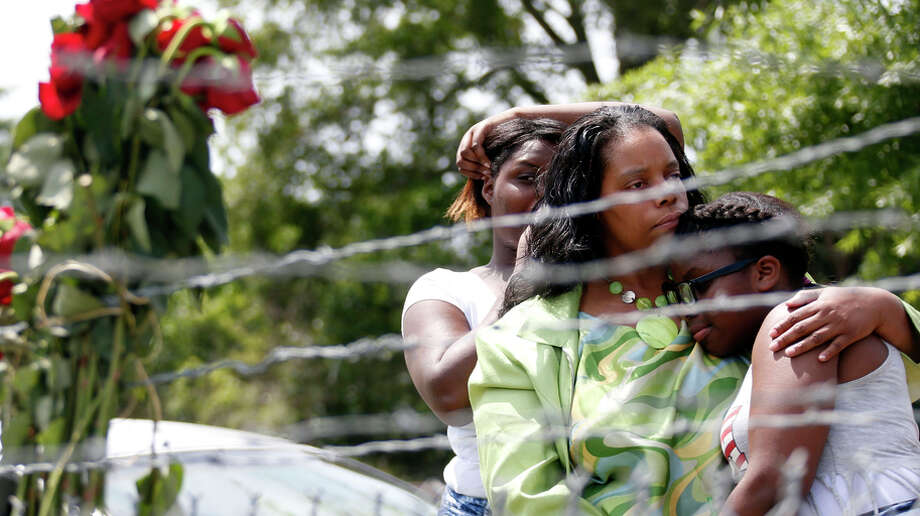 Waynetta Theodore (left), Alberta Harris and Christiena Preston pay their respects near where the officers were killed. Photo: Rogelio V. Solis / Associated Press / AP