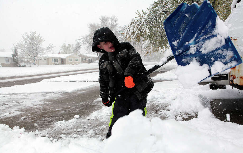 Josyah Puckett, 6, helps clear off his family's driveway in Rapid City, S.D. after the city saw nearly a foot of snow. Photo: Chris Huber / Associated Press / Rapid City Journal