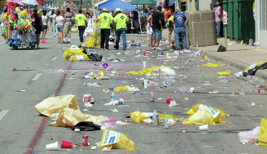 City employees and volunteers distributed some 14,000 yellow mesh recycling bags, more than twice the 6,000 recycling bags distributed last year, at the two major Fiesta street parades. The yellow bags were then placed in the middle of the street and loaded onto trucks after the daytime Battle of Flowers Parade and nighttime Fiesta Flambeau Parade. City and Fiesta officials are disappointed that the percentage of garbage recycled from the two events combined fell from 17 percent to 11 percent, according to a city report. Photo: Scott Huddleston, Staff / San Antonio Express-News / San Antonio Express-News