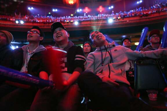 Audience members (left to right),Sanford Wong, Peter Cheung, and Eric Cheung get into the match at the Dota 2 (Defense of the Ancients) video game tournament to begin at the Warfield Theater in San Francisco, Calif., on Sunday, May 10, 2015.