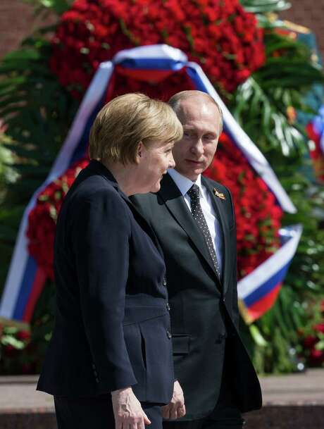 German Chancellor Angela Merkel and Russian President Vladimir Putin walk together Sunday at the Tomb of the Unknown Soldier in Moscow. Photo: Alexander Zemlianichenko, STF / AP