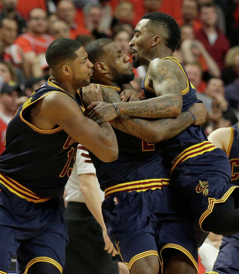 LeBron James (second from left) is mobbed after hitting the game-winner. Photo: Nam Y. Huh / Associated Press / AP
