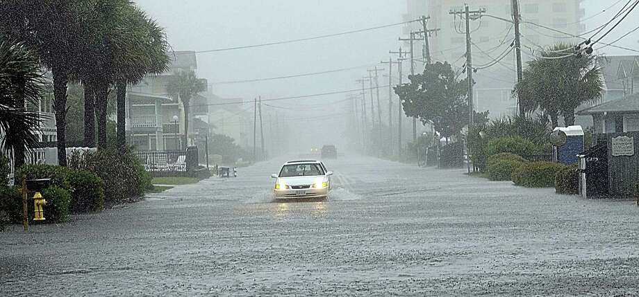 A car drives south on a flooded Ocean Boulevard after it went past barricades warning of the high water Sunday in North Myrtle Beach, S.C.  Photo: Charles Slate, MBR / The Sun News