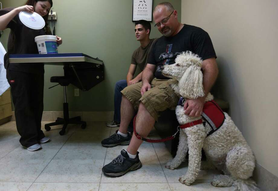 "Vet-tech Katherine Garza grabs a treat for ""Cali,"" a Paw Pals Assistance dog. Photo: Mayra Beltran, Staff / © 2015 Houston Chronicle"