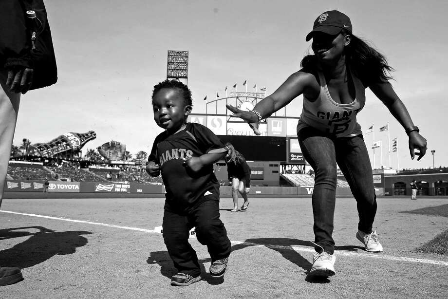 Ebony Marshall tries to get her son Kyson, 22 months, headed in the right direction while taking part in a Mother's Day running of the bases after the San Francisco Giants' 3-2 win over the Miami Marlins in an MLB game at AT&T Park in San Francisco, Calif., on Sunday, May 10, 2015. Photo: Scott Strazzante / The Chronicle / ONLINE_YES
