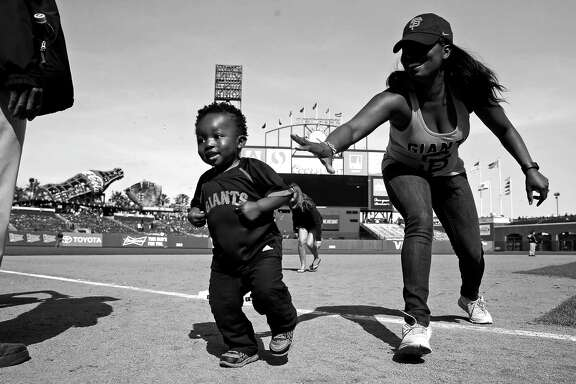 Ebony Marshall tries to get her son Kyson, 22 months, headed in the right direction while taking part in a Mother's Day running of the bases after the San Francisco Giants' 3-2 win over the Miami Marlins in an MLB game at AT&T Park in San Francisco, Calif., on Sunday, May 10, 2015.