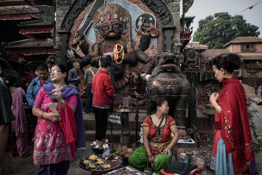 Devotees gather at the high stone image of Kala Bhairava at Durbar Square, in the historical centre of Kathmandu on May 10, 2015. The 7.8 magnitude earthquake which struck the Himalayan nation on April 25, 2015 has had a devastating impact on the economy of Nepal where tourism attracted almost 800,000 foreign visitors in 2013 -- many of them climbers heading straight to Mount Everest but also less adventurous tourists seeking the rich cultural history of Kathmandu.