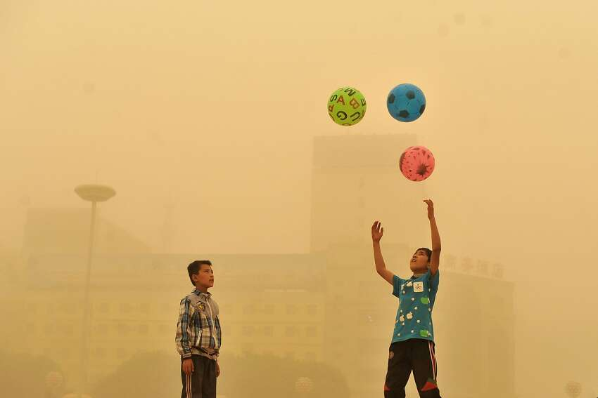 A boy watches as another boy play with balls, during a sandstorm in Kashgar city in northwestern China's Xinjiang Uighur Autonomous Region, Sunday, May 10, 2015.