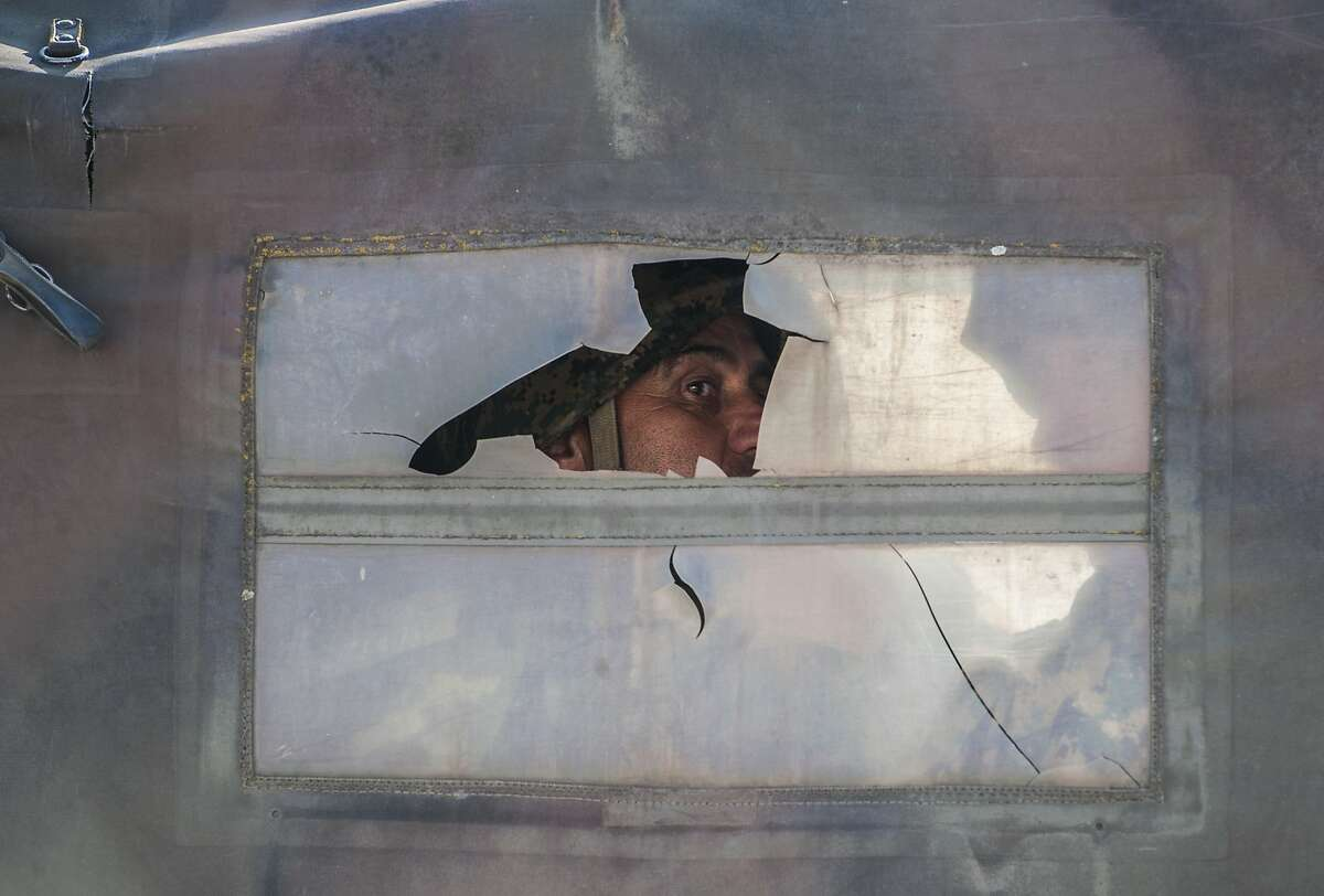 A Macedonian police officer looks out of a ripped truck window in Kumanovo on May 10, 2015. Shooting broke out for a second day on May 10 in north Macedonia as concern mounted in Europe after clashes between police and unidentified gunmen that erupted on May 9 at dawn in the restive north of Macedonia. Eight policemen and 14 gunmen have been killed in two days of clashes, police said on Sunday.