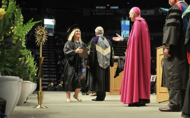Graduate Ashley Hiller walks across the stage with her diploma  as she goes to shake hands with Albany Bishop Emeritus Howard Hubbard during Siena College commencement at the Times Union Center on Sunday, May 10, 2015, in Albany, N.Y.  (Paul Buckowski / Times Union) Photo: PAUL BUCKOWSKI / 00031513A