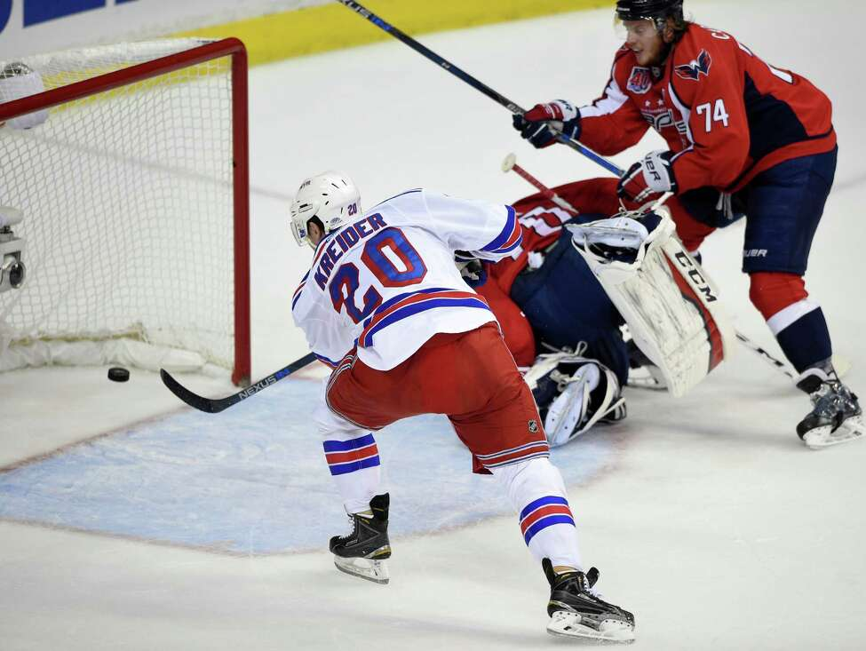 New York Rangers left wing Chris Kreider (20) scores his second goal of the period during the first period past Washington Capitals goalie Braden Holtby (70), center, and John Carlson (74) in Game 6 in the second round of the NHL Stanley Cup hockey playoffs, Sunday, May 10, 2015, in Washington. (AP Photo/Nick Wass) ORG XMIT: VZN205