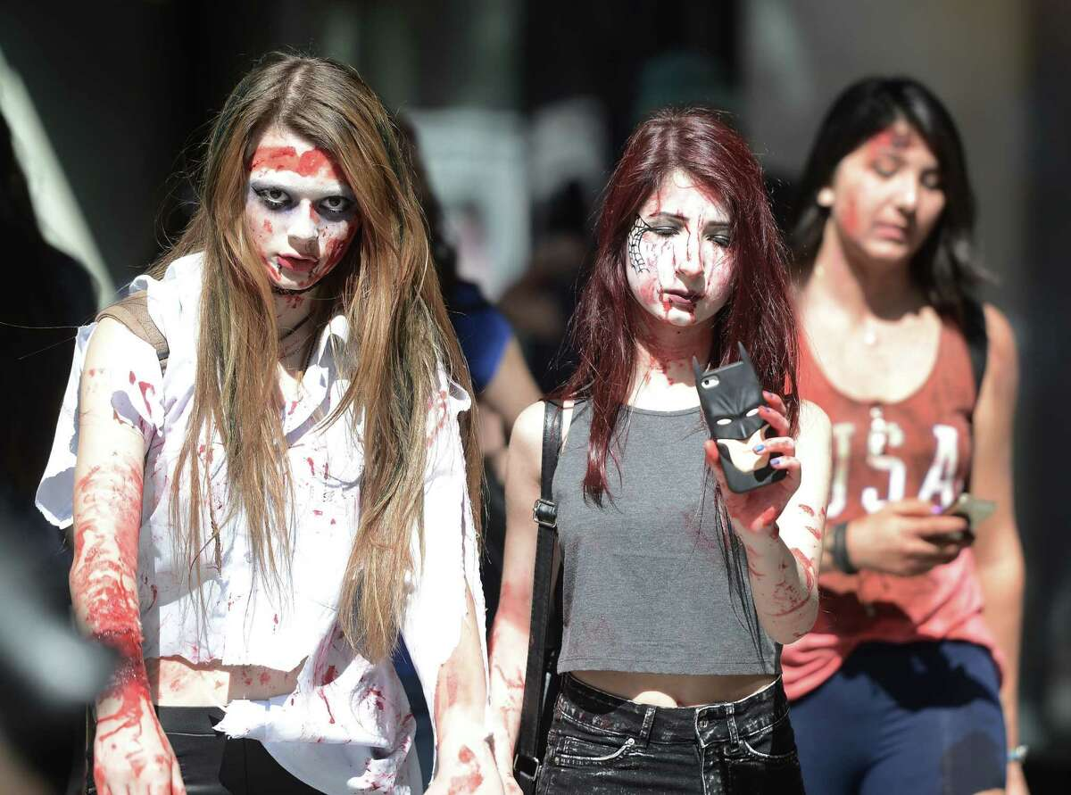 People with zombie makeup and costumes are seen during